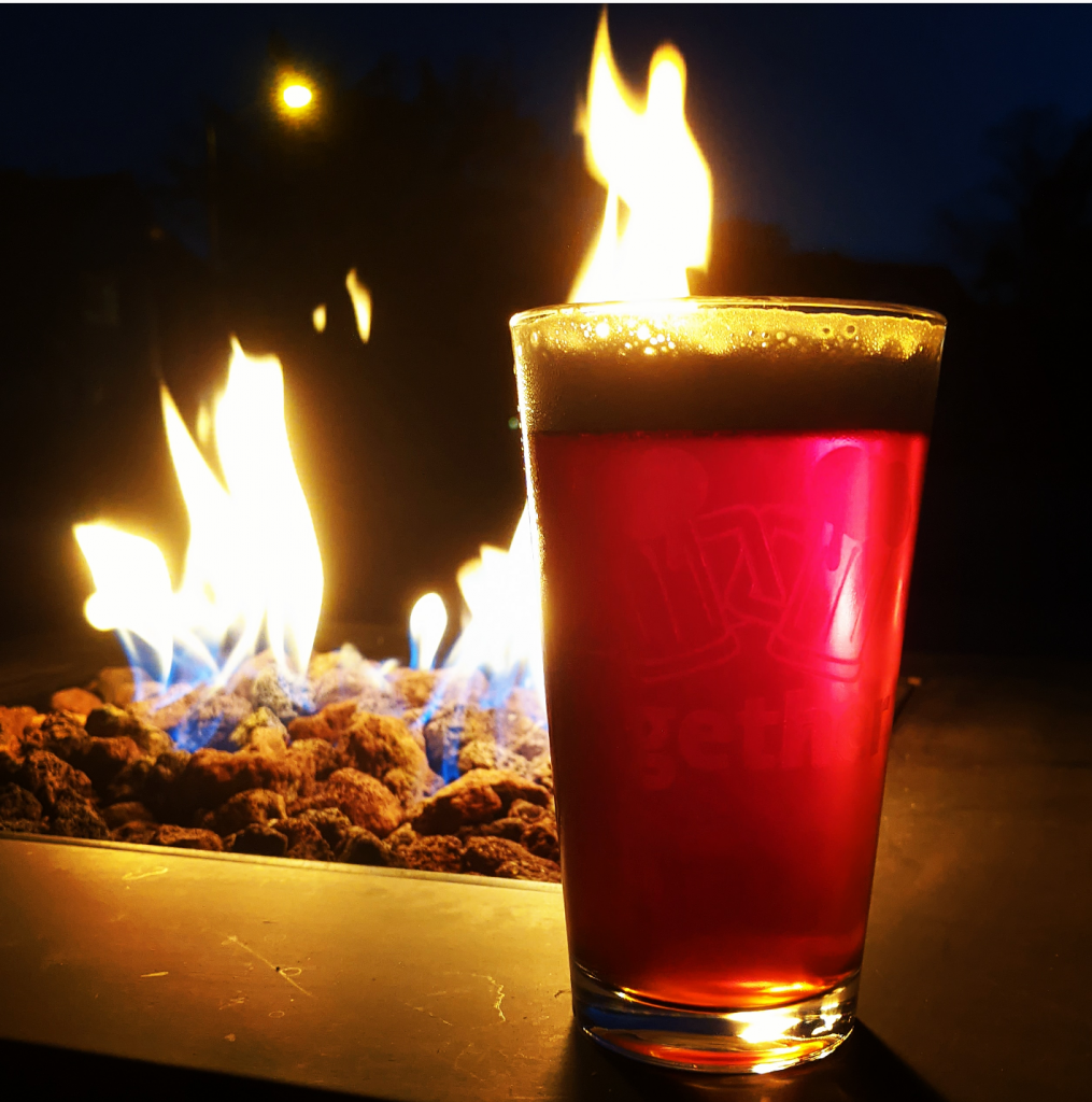 A pint of Smoke Signal IPA in front of a fire.
