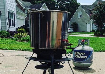 A propane burner, propane tank, and kettle being used for homebrewing showing the differences between electric vs gas homebrewing systems